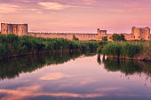 Scenic sunset view of the ancient city wall of the Aigues-Mortes, famous medieval fortress in South France, Camargue national park