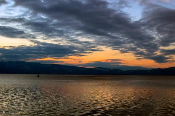 ein malerischen sonnenuntergang mit einer schwarzen wolke über die letzten sonnenstrahlen spiegeln sich in ohrid-see. - disaster design stock-fotos und bilder
