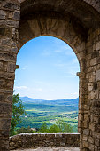 Scenic Tuscany landscape framed with stone arc port, Val d'Orcia, Italy