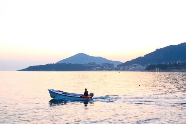 scenic view at sea with fishman in boat - fishman imagens e fotografias de stock