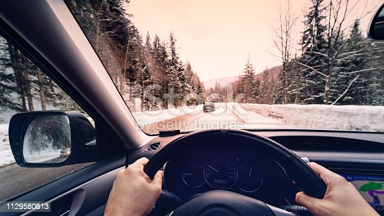 1066508460 istock photo scenic view of a road with snow covered landscape while snowing in winter season -  POV, first person view shot 1129580813
