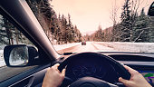 scenic view of a road with snow covered landscape while snowing in winter season - view from the car -  POV, first person view shot