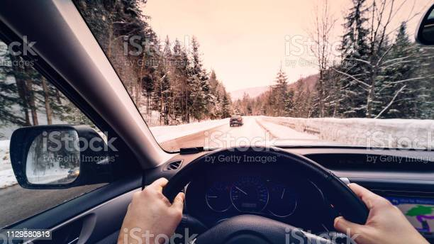 Photo of scenic view of a road with snow covered landscape while snowing in winter season -  POV, first person view shot