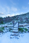 A scenic view of a snowy wooden bridge with stone step over a torrential stream with mountain slope in the background under a majestic blue sky and white clouds