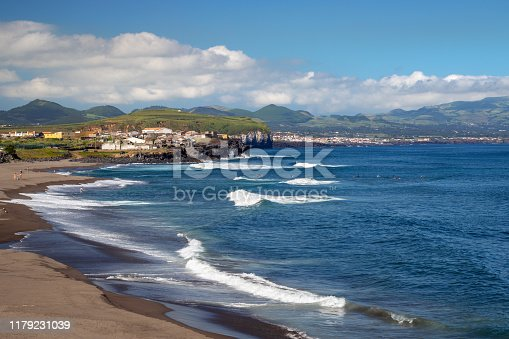 Beautiful scenic landscape of Atlantic ocean and coastline on sunny day. Unidentified surfers waiting for a wave by Ribeira Grande town on north coast of Sao Miguel island, Azores.
