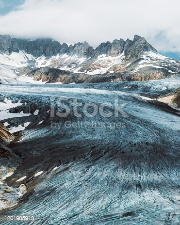 Dramatic view of Rhone melting glacier, blue glacial lake and the Swiss Alps at Furka Pass, Switzerland