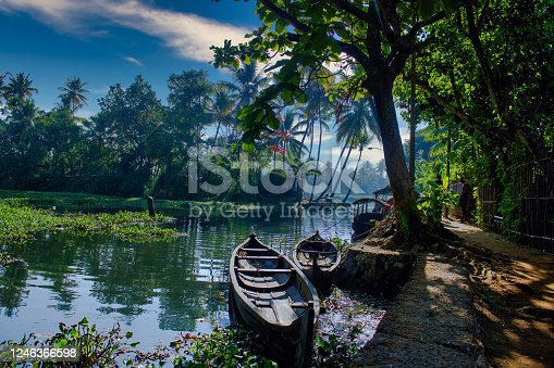 A scenic view of boats under a blue sky in backwaters situated in Allepey town located in Kerala state, India