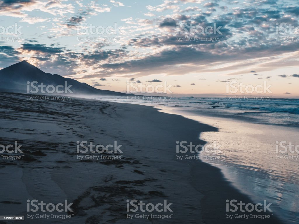 Scenic view of calm ocean and black sand beach. Clouds reflecting in the water. Beautiful sunset in Ajuy in Fuerteventura, Canary Islands, Spain. - Royalty-free Atlantic Ocean Stock Photo