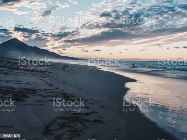 Scenic View Of Calm Ocean And Black Sand Beach Clouds Reflecting In The Water Beautiful Sunset In Ajuy In Fuerteventura Canary Islands Spain Stock Photo - Download Image Now