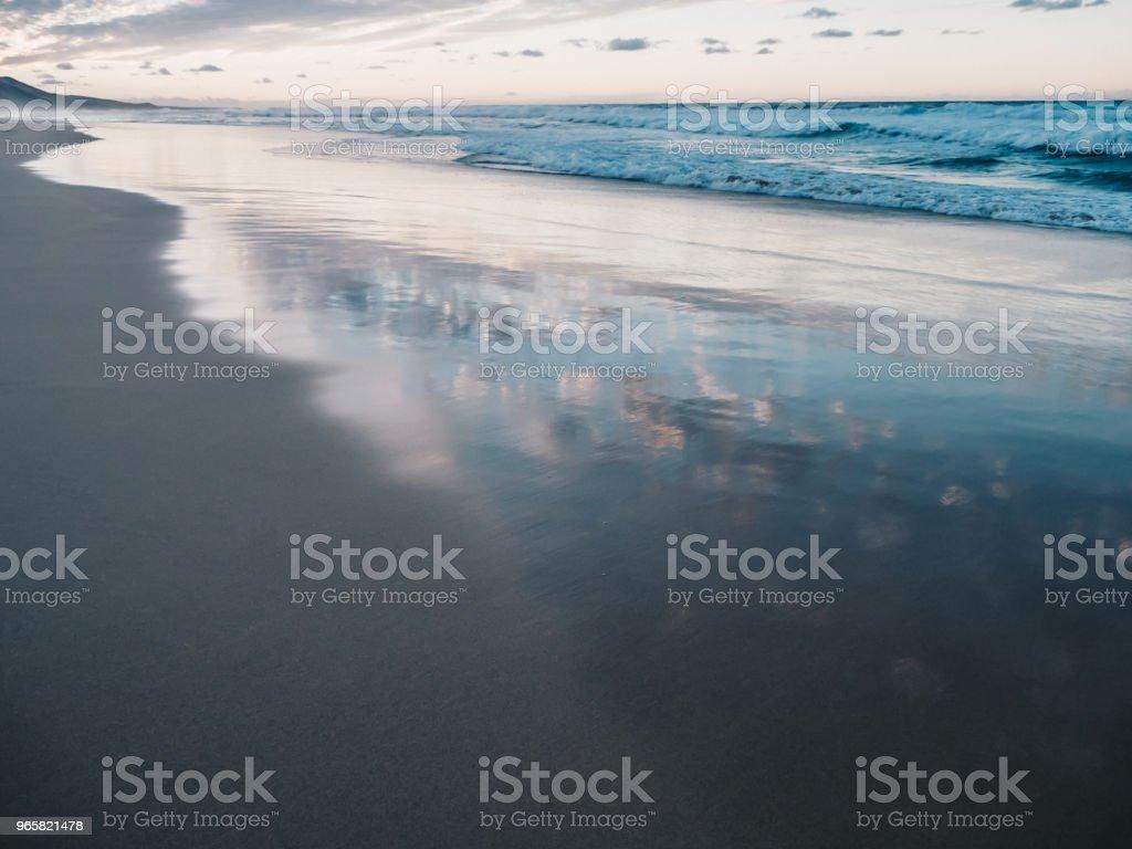 Schilderachtig uitzicht op rustige Oceaan en zwarte zand strand van Ajuy in Fuerteventura, Canarische eilanden, Spanje. Wolken weerspiegelt in het water - Royalty-free Atlantische oceaan Stockfoto