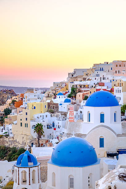 Scenic view of colorful houses and blue domes at sunset stock photo