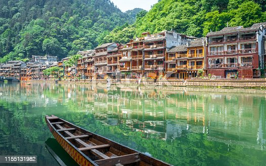 Scenic view of Fenghuang phoenix ancient town with Tuo Jiang river boat and old houses in Hunan China