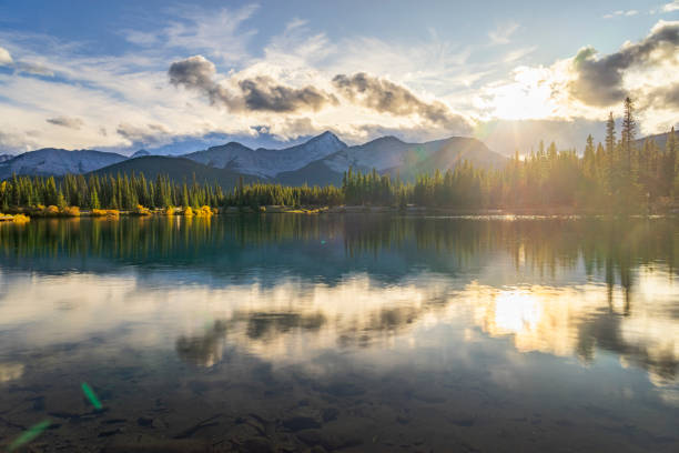 Scenic View Of Forget-Me-Not Pond at twilight Backlit shot of snow-capped mountains and pine trees reflected in the beautiful Forget-Me-Not-Pond, located in Kananaskis Country,Alberta,Canada. kananaskis country stock pictures, royalty-free photos & images
