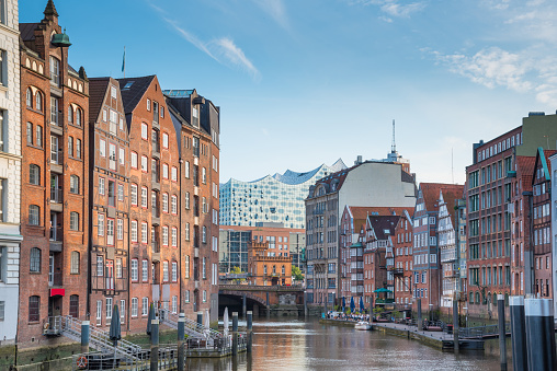 scenic view of historic buildings on both sides of Nikolaifleet channel in Hamburg, Germany with Elbphilharmonie concert hall in background under beautiful summer sky