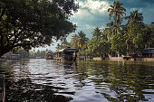 A scenic view of house boat under a dramatic sky in backwaters situated in Allepey town located in Kerala state, India