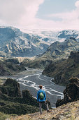 Scenic view of man in blue raincoat looking at Thórsmörk river valley in Iceland Highlands