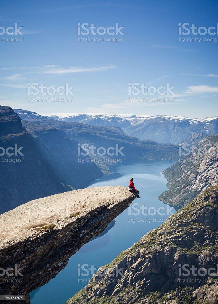 Scenic view of man sitting on Trolltunga Rock in Norway stock photo