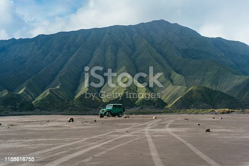 Scenic view of old-fashioned SUV driving through desert near Bromo volcano