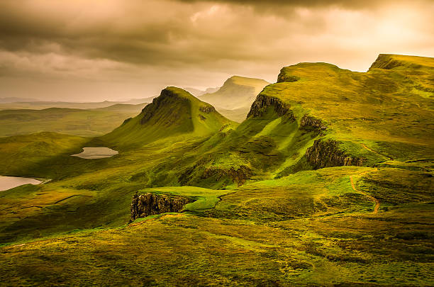 Scenic view of Quiraing mountains sunset with dramatic sky, Scot Scenic view of Quiraing mountains sunset with dramatic sky in Scottish highlands, Isle of Skye, United Kingdom scottish highlands stock pictures, royalty-free photos & images