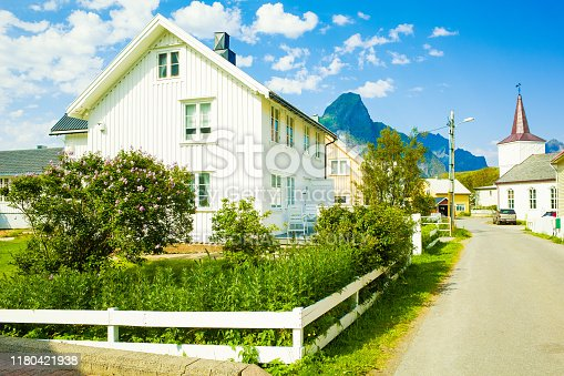 Reine, Norway - July 18, 2018: Traditional Norwegian wooden houses against the background of steep cliffs, Lofoten Islands