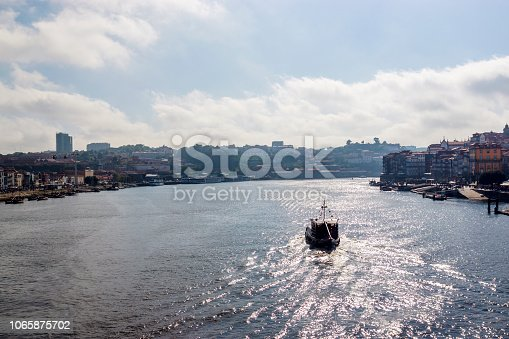 Scenic view of Ribeira and Vila Nova de Gaia from Dom Luis I Bridge in a sunlight. Porto, Portugal. The boat is floating on the river Douro. Travel photography.