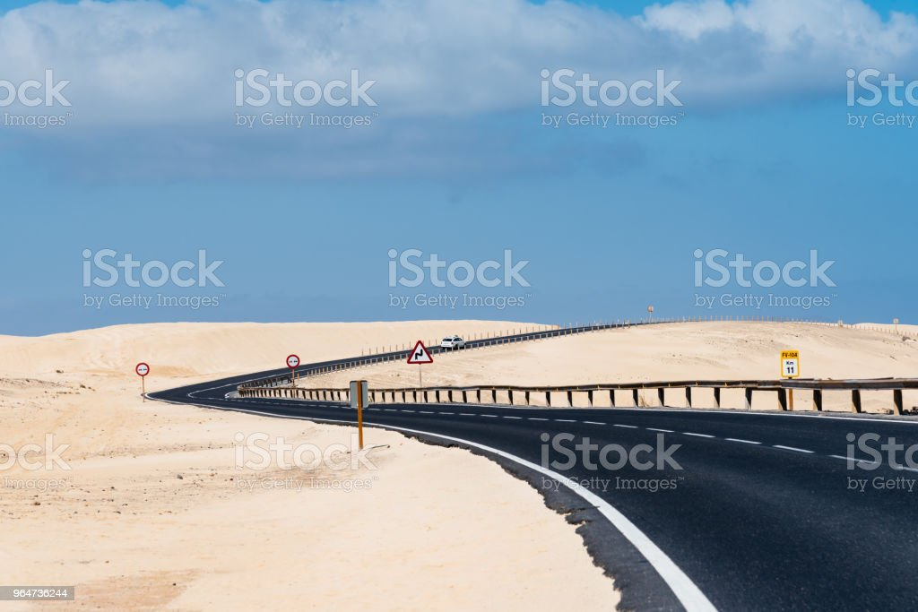 Scenic view of road through sand dunes against sky royalty-free stock photo