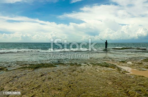 scenic view of rocky seashore with man silhouette in the horizon fishing with rod relaxed at amazing beautiful tropical beach in Summer holidays travel and relaxing hobby concept