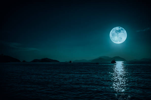 Scenic view of small boat in calm sea water at night time and super moon. serenity nature background. stock photo