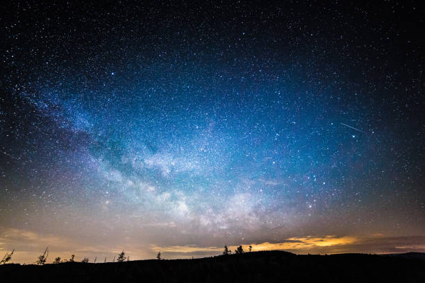 Scenic view of starry night sky over wide landscape stock photo