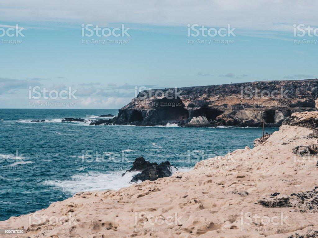 Schilderachtig uitzicht op steenachtige oever met zwarte grotten. Blauwe zee golven slaan de kliffen. Fuerteventura, Spanje - Royalty-free Atlantische oceaan Stockfoto