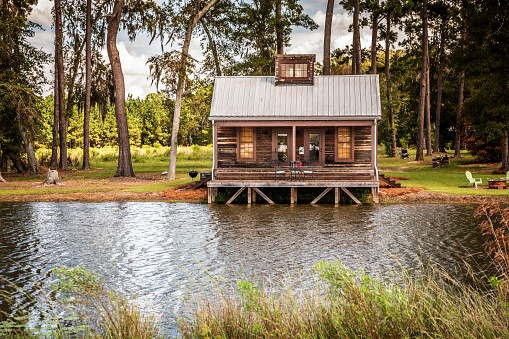 Scenic view of the exterior of a rural rustic wooden camp house used for fishing and hunting. The house is located on a large pond