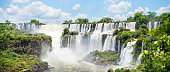 Scenic view of the breathtaking Iguazu Falls crashing onto rocks in the rainforest on a sunny day