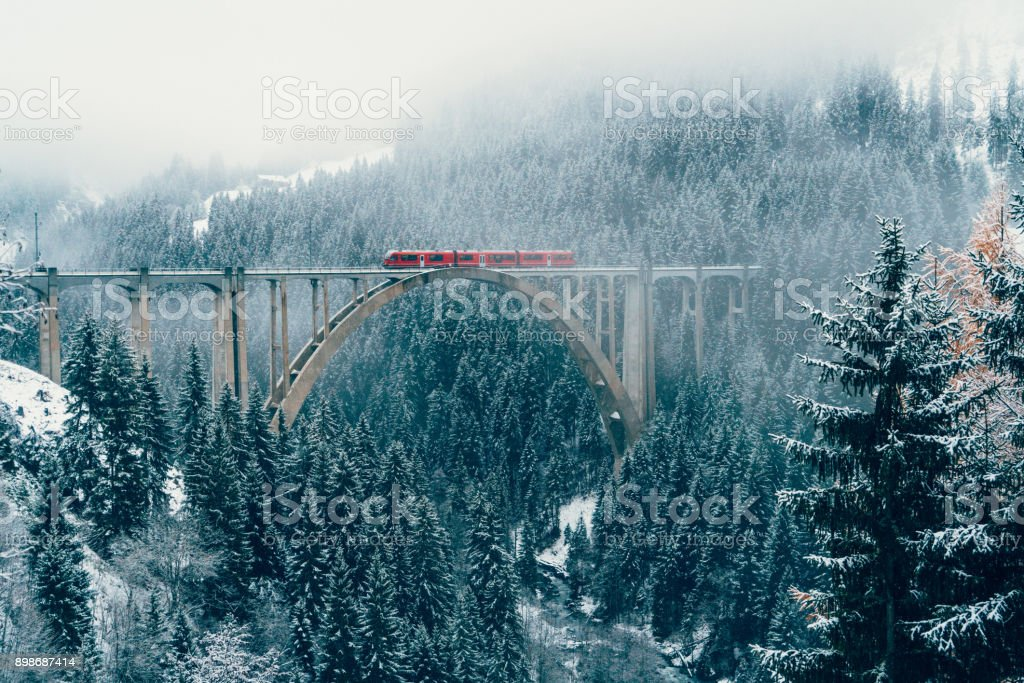 Scenic view of train on viaduct in Switzerland Scenic view of train on viaduct in Switzerland forest in winter Beauty In Nature Stock Photo