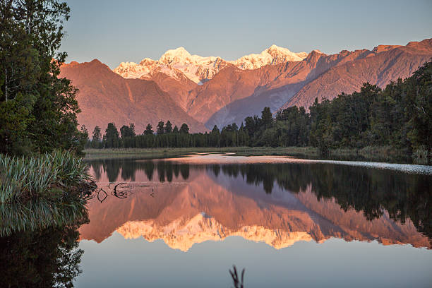 scenic view of trees and mountains reflection in lake matheson - lac mirror lake photos et images de collection