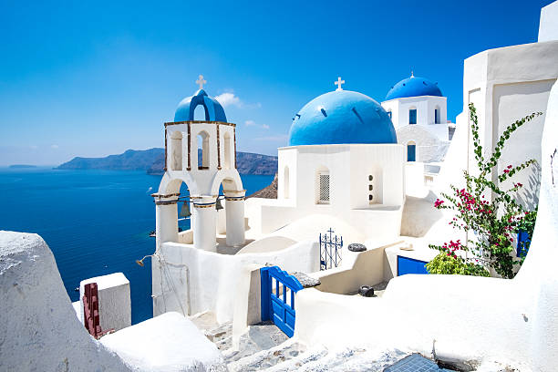 scenic view of white houses and blue domes on santorini - griekenland stockfoto's en -beelden