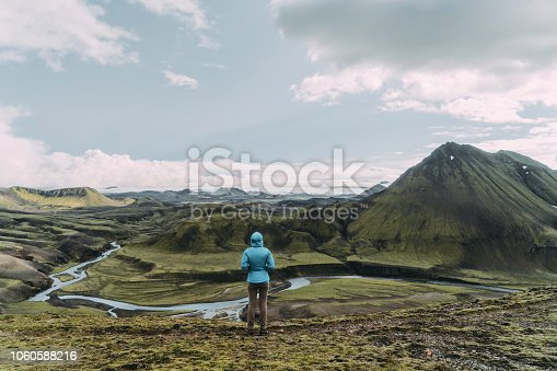 Scenic view of woman in blue raincoat looking at Thórsmörk river valley in Iceland Highlands