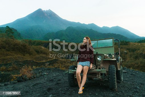 Scenic view of young Caucasian  woman sitting on old fashioned SUV near Merapi volcano at sunrise