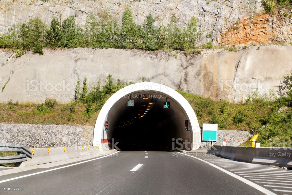 Scenic view on entrance to the tunnel and highway road leading through in Croatia, Europe / Transport and traffic infrastructure / Signs and signaling. stock photo