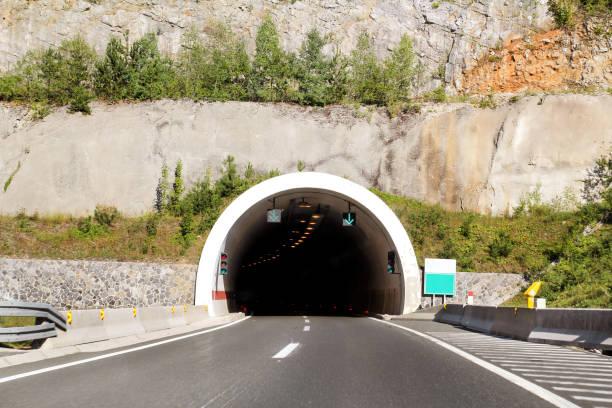 Vista panorâmica na entrada do túnel e rodovia estrada que conduz através da Croácia, Europa / infra-estrutura de transporte e trânsito / sinais e sinalização. - foto de acervo
