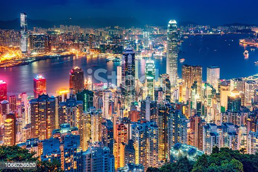 Scenic view on Hong Kong island, China, by night. Multicolored nighttime skyline with illuminated skyscrapers seen from Victoria Peak
