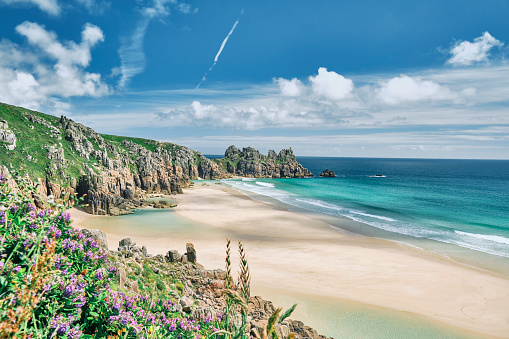 Scenic views across Pedn Vounder Beach towards Logan's Rock, Cornwall on a sunny June day.