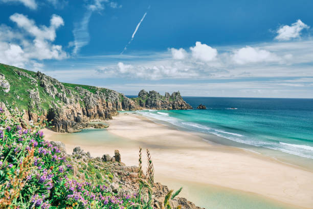 Scenic views across Pedn Vounder Beach towards Logan's Rock, Cornwall on a sunny June day. stock photo