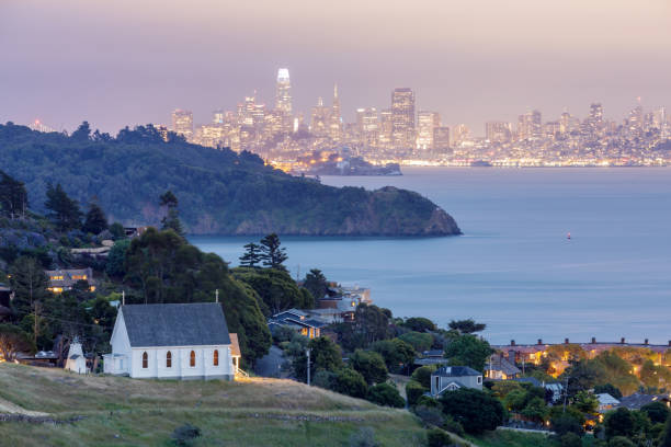 Scenic views of Old St Hillary's Church, Angel Island, Alcatraz Prison, San Francisco Bay and San Francisco Skyline at dusk. stock photo