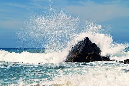 Scenic water splash and a rock in ocean