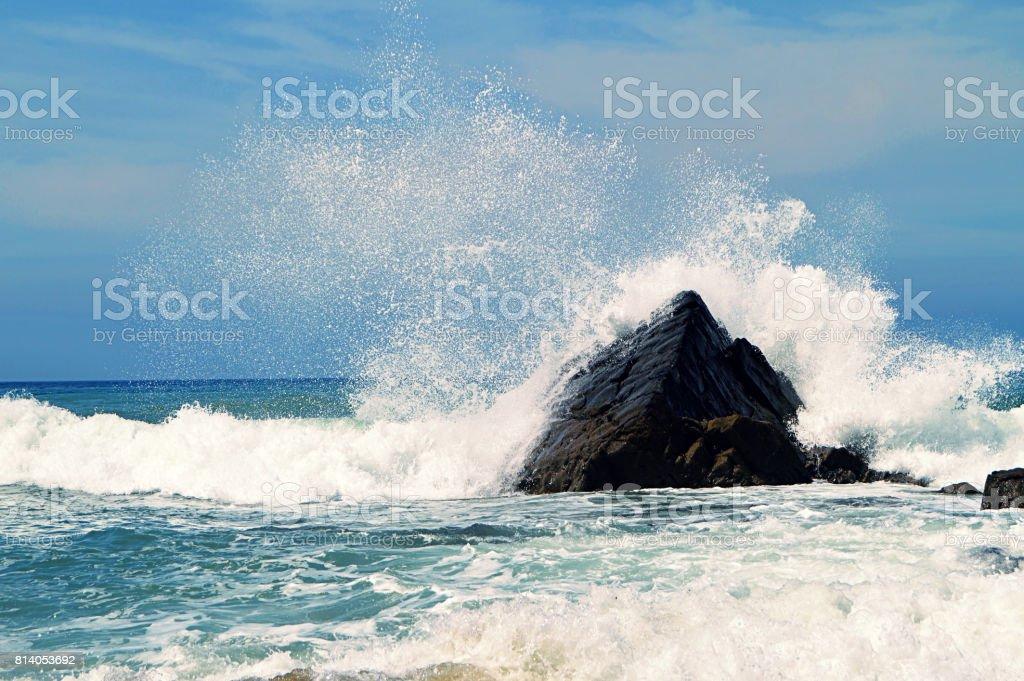 Scenic water splash and a rock in ocean stock photo