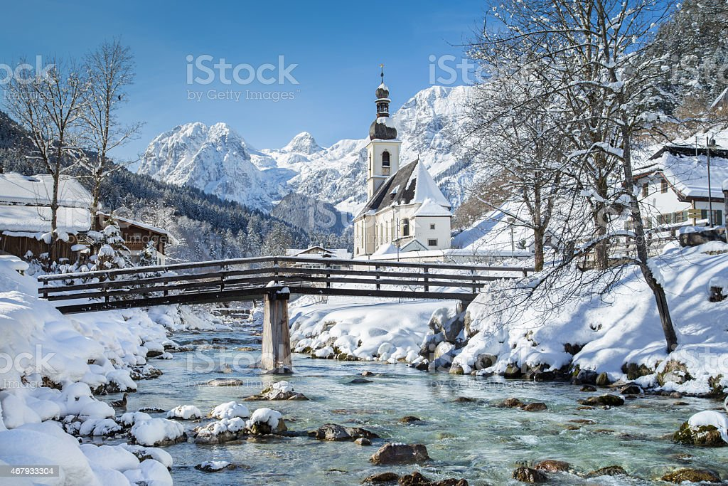 Scenic winter landscape in the Alps with church stock photo