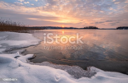 Scenic winter landscape with frozen lake and sunset at evening time in Finland