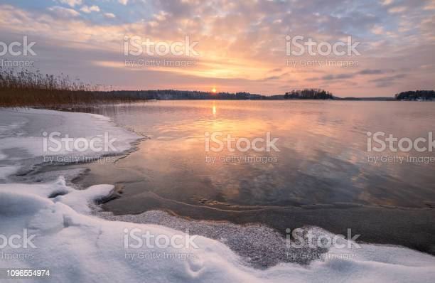 Photo of Scenic winter landscape with frozen lake and sunset at evening time in Finland