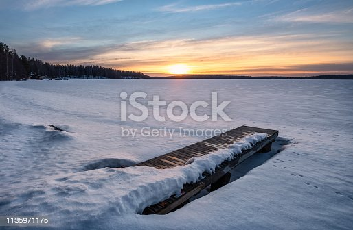 Scenic winter landscape with pier and sunset at evening light in Finland