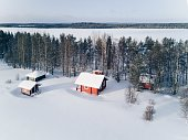 Scenic winter picture of a cottage near the lake and trees covered in snow. Finland